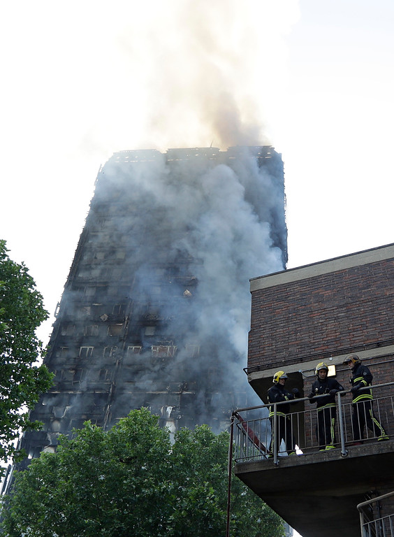 . Firefighters in place as they battle a massive fire that raged in a high-rise apartment building in London, Wednesday, June 14, 2017. Fire swept through a high-rise apartment building in west London early Wednesday, killing an unknown number of people and sending more than 50 people to area hospitals. (AP Photo/Matt Dunham)