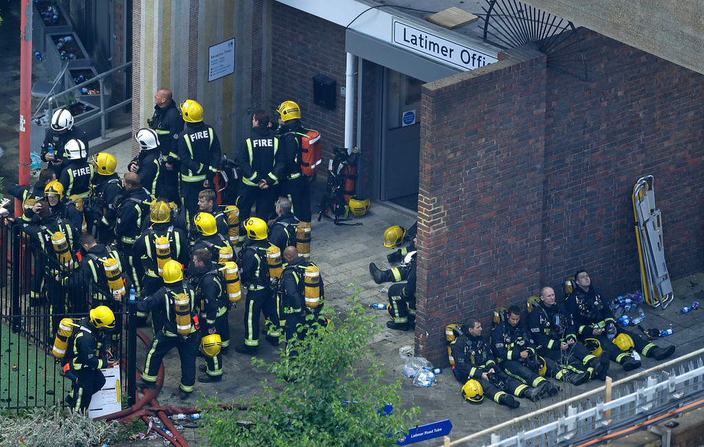 . Firefighters rest as they take a break in battling a massive fire that raged in a 27-floor high-rise apartment building in London, Wednesday, June 14, 2017. Fire swept through a high-rise apartment building in west London early Wednesday, killing an unknown number of people and sending more than 50 people to area hospitals. (AP Photo/Matt Dunham)