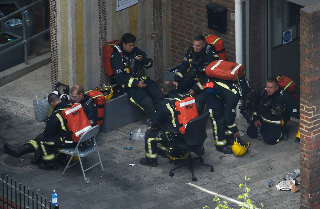 . Fire crews rest as they take part in the operation to put out a fire in a high rise apartment block in London, Wednesday, June 14, 2017.  Firefighters are battling a huge blaze at a west London high-rise block that houses more than 100 apartments. (AP Photo/Alastair Grant)