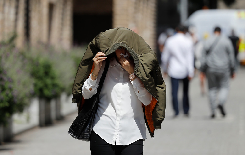 . A woman covers her head and face as protection from the smoke near the high-rise apartment building where a massive fire raged overnight, in London, Wednesday, June 14, 2017. A deadly overnight fire raced through a 24-story apartment tower in London on Wednesday, killing at least six people and injuring more than 70 others. (AP Photo/Frank Augstein)