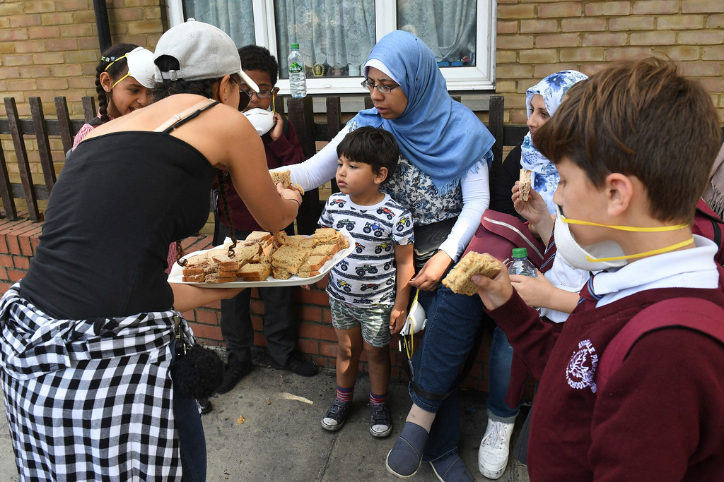. Sandwiches are handed out to local residents close to a fire that has engulfed the 24-storey  Grenfell Tower in west London, Wednesday June 14, 2017. Fire swept through a high-rise apartment building in west London early Wednesday, killing an unknown number of people with around 50 people being taken to hospital. (Victoria Jones/PA via AP)