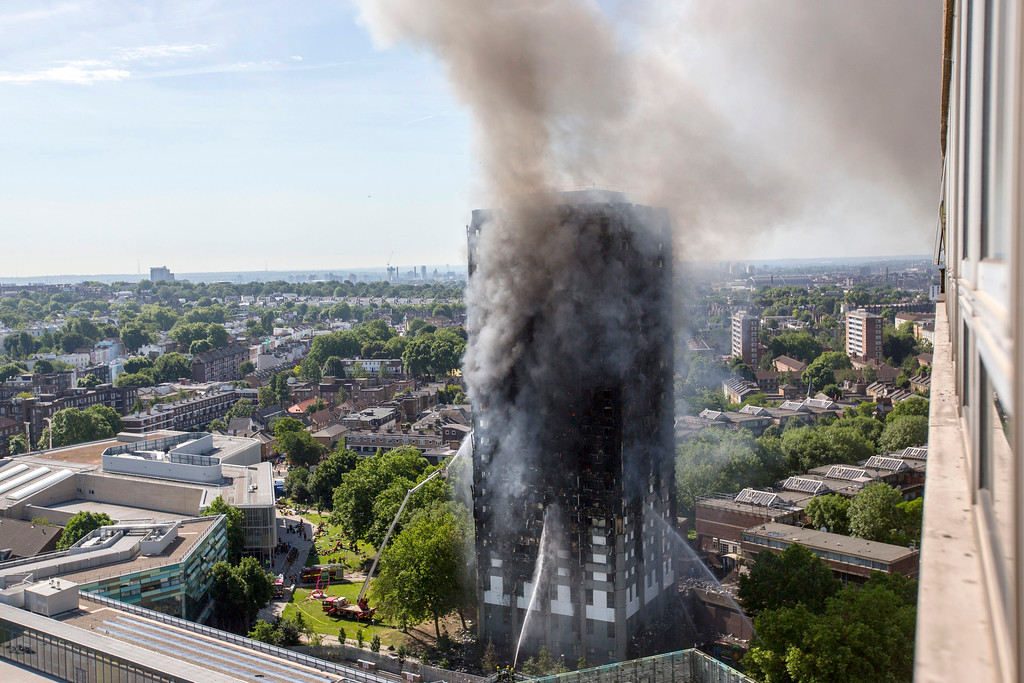 . Smoke billows from a high-rise apartment building on fire in west London Wednesday, June 14, 2017. Fire swept through the high-rise apartment building early Wednesday, sending dozens people to area hospitals. (Rick Findler/PA via AP)