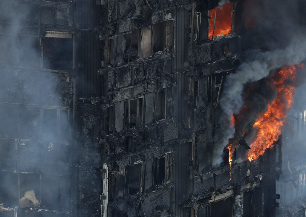 . Smoke and flames billow from a massive fire that raged in a high-rise apartment building in London, Wednesday, June 14, 2017. A deadly night-time fire raced through a 24-story apartment tower in London early Wednesday, killing at least six people and injuring dozens more. (AP Photo/Matt Dunham)