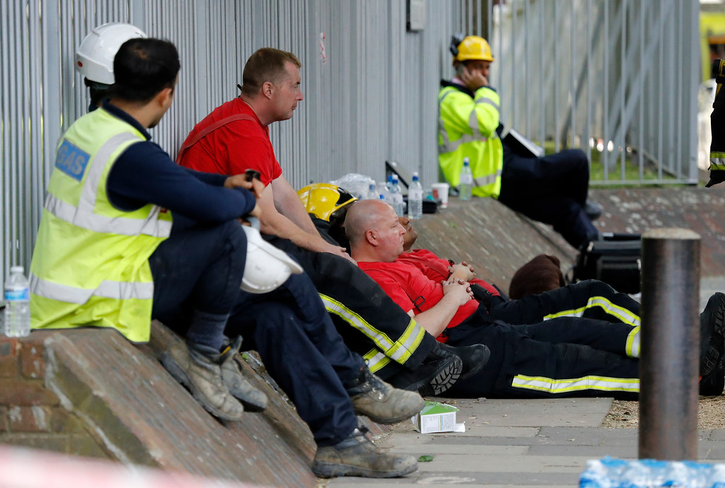 . Emergency services officers take a rest near to the high-rise apartment building where a massive fire raged, in London, Wednesday, June 14, 2017. A deadly overnight fire raced through a 24-story apartment tower in London on Wednesday, killing at least six people and injuring more than 70 others. (AP Photo/Frank Augstein)