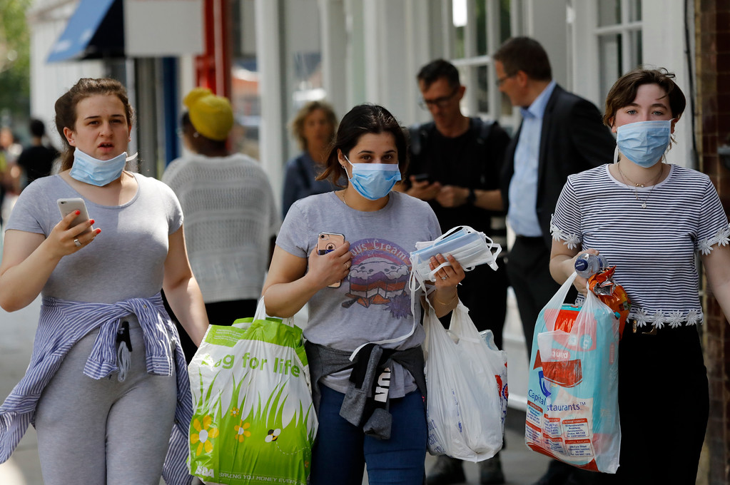 . Women wearing masks to protect from the smoke, walk near to the high-rise apartment building where a massive fire raged, in London, Wednesday, June 14, 2017. A deadly overnight fire raced through a 24-story apartment tower in London on Wednesday, killing at least six people and injuring more than 70 others. (AP Photo/Frank Augstein)