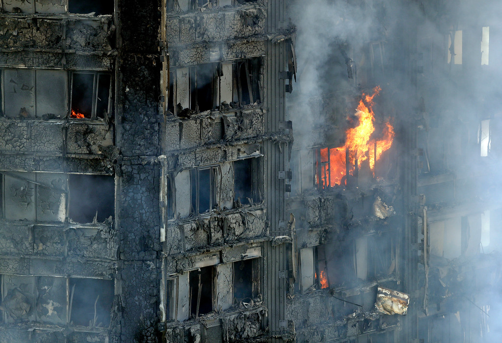 . Smoke and flames billow from a massive fire that raged in a 27-floor high-rise apartment building in London, Wednesday, June 14, 2017. Fire swept through a high-rise apartment building in west London early Wednesday, killing an unknown number of people and sending more than 50 people to area hospitals. (AP Photo/Matt Dunham)