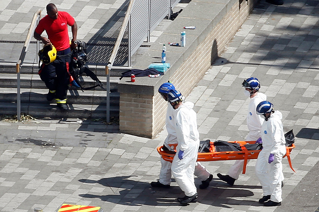 . Members of the forensic team move a body near the scene of a fire at a high rise apartment block, in London, Wednesday, June 14, 2017. Firefighters are battling a huge blaze at a west London high-rise block that houses more than 100 apartments. (AP Photo/Alastair Grant)