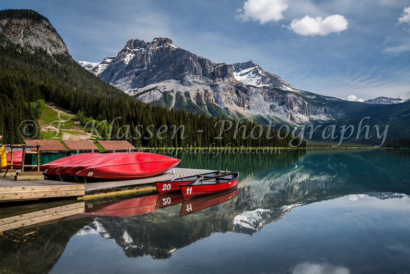 Canoes on the dock with mountain reflections in Emerald Lake, Yoho National Park, British Columbia, Canada.
