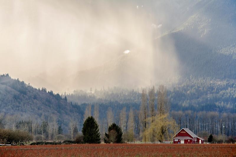 Rain falling in the mountains behind farmland