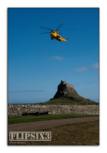 RAF rescue helicopter over Holy Island Castle