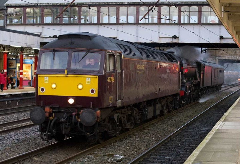 47746 Chris Fudge & 60103 Flying Scotsman, 5Z72, Lancaster, Wed 27 January 2016 1 - 1637. A cheerful wave from the diesel driver as Flying Scotsman makes its first main line appearance for 10 years as it is taken from the East Lancashire Railway to Carnforth Steamtown.