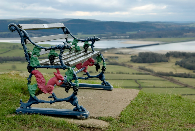 Replica Furness Railway bench, Ulverston, 27 January 2006. Looking east towards Leven viaduct.  The Furness used this distinctive squirrel and grape design for its benches.  Replicas are now commercially available.