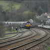 EWS liveried Class 66/0 (66002) slowly eases its train of empty china clay wagons off the Fowey branch and runs 'wrong' line into Lostwithiel Station prior to running round its train in the down loop - 28 March 2006.