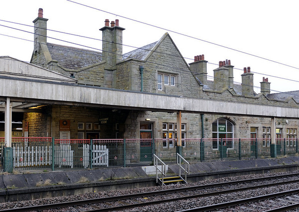 Welcome to Carnforth Station visitor centre! Thurs 16 February 2012.  The centre occupies these buildings, which date from the station's rebuilding in 1880.  In later years they became derelict and were very nearly demolished.  But they were rescued and restored, and the visitor centre opened in 2003.  The 125mph West Coast Main line from London to Glasgow is in the foreground, with a refuge for track workers.