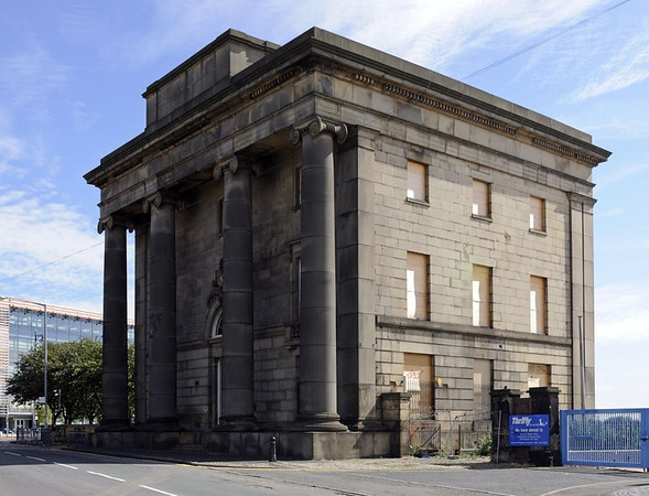 London & Birmingham Rly station, Curzon Street, Birmingham, Sun 26 June 2011 1.  Looking north east.  These offices were built in 1838 for the opening of the London & Birmingham to a design by Philip Hardwicke.  They were intended to complement his much-missed Euston arch at the other end of the L & B.  Originally the building was flanked by arches and an hotel, and had a trainshed behind - all long gone.  Regular passenger services ceased in 1854 when New Street station opened, and it was subsequently part of the LNWR's goods depot.  Out of use and boarded up at the time of this photo, the building is listed grade 2.   The Thinktank science and technology museum in which 46235 City of Birmingham is immured can be seen in the left distance.