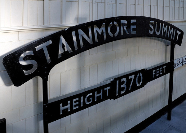 Stainmore summit sign, Darlington North Road, 15 November 2009     Stainmore summit was the highest on an English main line.   It was on the trans-Pennine South Durham & Lancashire Union Rly line opened in 1861 by the Stockton & Darlington to carry Durham coke west and Cumberland iron ore and pig iron east.  The line ran from Barnard Castle over Stainmore to Kirkby Stephen, where it divided, with branches running to Tebay and to Penrith.  At Tebay it joined the London & North Western's Crewe - Carlisle line, from which it gained access to the Furness Rly to Barrow.  At Penrith it joined (also via the LNWR) the Cockermouth, Keswick and Penrith Rly, from which it gained access to the raiways of west Cumberland.  The Stainmore line closed in 1962.
