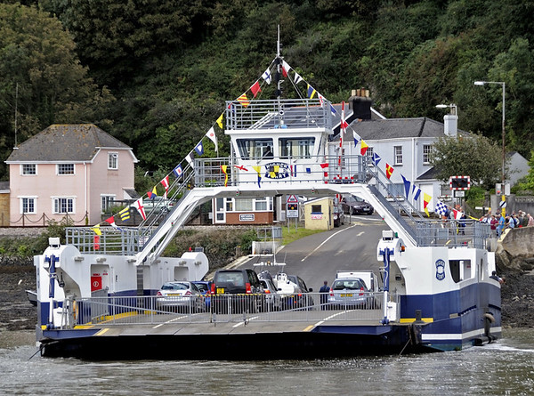 Dartmouth higher ferry, Britannia crossing, Greenway, Sun 2 September 2012.   The higher ferry connects the A379 on either side of the River Dart.  The ship seen here entered service in 2009, and is guided by the cables visible on either side.  It is owned and operated by the Dartmouth - Kingswear Floating Bridge Co.  The  A379 crosses the Dartmouth Steam Railway immediately beyond the slipway.  Just visible is Britannia crossing signal cabin from which the railway is controlled.
