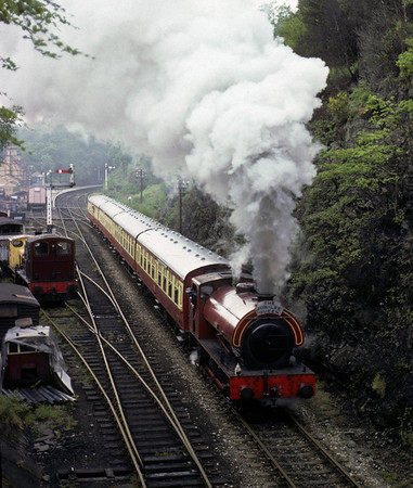Cumbria, Haverthwaite, 11 June 1977.     Sporting a 'Jubilee Queen' headboard in honour of the Queen's Silver Jubilee, the Hunslet (3794 / 1953) sets off with the first train of the day.  In 2012 this loco was based on the Ribble Steam Rly, Preston. Photo by Les Tindall.