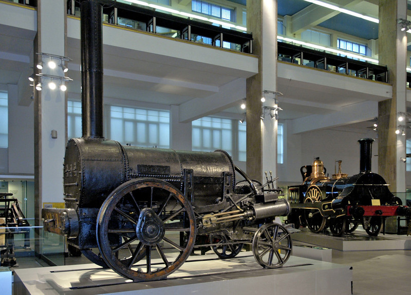 Rocket, Science Museum, London, 28 January 2005.      This is the original 1829 Stephenson loco, clear winner of the Rainhill trials.  It is preserved with extensive modifications, in particular its cylinders were lowered for steadier running.  Beyond is Francis Trevithick's 1845 London & North Western Rly 2-2-2 No 1848, oringinally Grand Junction Rly No 49 Columbine.
