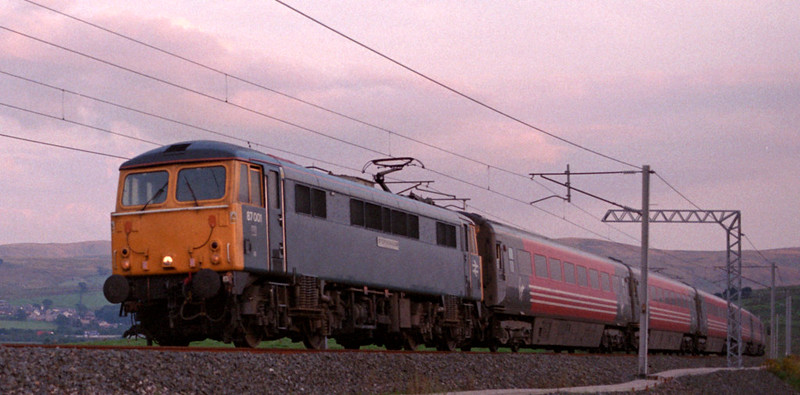 87001 Stephenson, 1S86, Greenholme, Fri 15 August 2003 - 2015.   Now with its first name reinstated, the pioneer 87 races up Shap with Virgin's 1630 Euston - Glasgow.