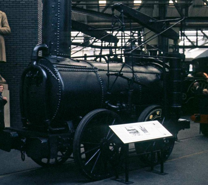 Agenoria, National Railway Museum, York, 2 October 1976.  Agenoria is the oldest loco in the NRM.  It was built in 1829, the same year as Rocket, for the Shutt End colliery, Kingswinsford, Staffordshire, by Foster, Rastrick & Co of Stourbridge.  They built only four locos, but the other three were exported to the Delaware & Hudson Canal Company where one of them, Stourbridge Lion, became the first loco to run in the USA.  Agenoria is believed to be practically identical with Stourbridge Lion.  Unlike the American locos, Agenoria had a long life, working until about 1864.  Like Puffing Billy it has vertical cylinders, but the wheels are coupled by a rod.  The loco had previously been displayed in the old York railway museum,  It was still at NRM York in 2017.  Photo by Les Tindall.