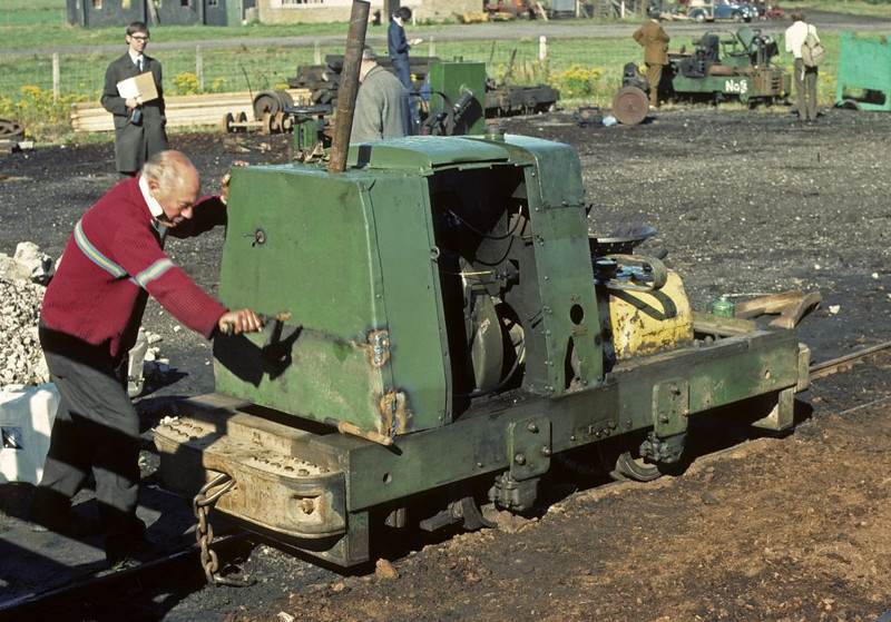 Starting an unidentified 2 foot gauge Ruston 4wDM with a crank handle, Cumberland Moss Litter Industry Limited, Kirkbride, Wigton, 31 July 1976.  Photo by Les Tindall.