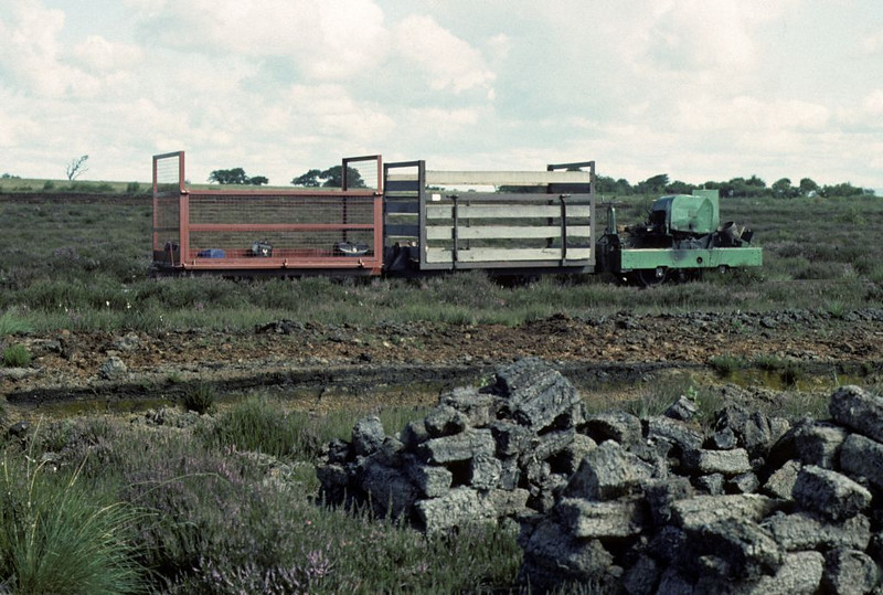 Motor Rail 7463 waits on the moss with the IRS train, Cumberland Moss Litter Industry Limited, Kirkbride, Wigton, 31 July 1976.  Photo by Les Tindall.