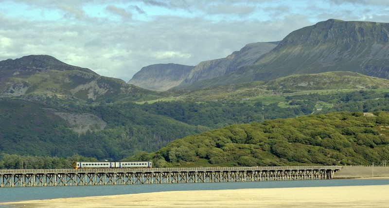 Barmouth bridge and Cader Idris from Barmouth Ferry, Wed 24 August 2011 - 1708.  A class 158 DMU approaches Morfa Mawddach with Arriva Trains Wales's 1534 Pwllheli - Machynlleth.