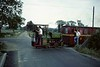 Pixie, Leighton Buzzard Light Railway, 25 July 1976 1.  The 2 foot gauge Kerr Stuart 0-4-0ST 4260 / 1922 crosses a minor road near the Stonehenge workshops with the last train of the day.  Photo by Les Tindall.