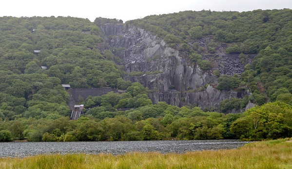 Dinorwic slate quarry, Sun 21 August 2011.  This view across Llyn Padarn completely fails to show the enormous size of the quarry.  Suffice to say that Elidir Fawr, into which it has been gouged, is some 2500 ft high, and that at its peak the quarry employed over 3000 men.  There was a very extensive 2ft gauge railway system within the quarry.  Slate was taken down the inclines seen at left to the 4ft gauge Padarn Rly which ran alongside the lake to Penscoins for export to all parts of the world from Port Dinorwic (now Felinheli).  The Llanberis Lake Rly now runs along part of the Padarn Rly trackbed.  After a long decline the quarry closed in 1969.  Much of its equipment was saved, and forms the basis for today's slate museum.