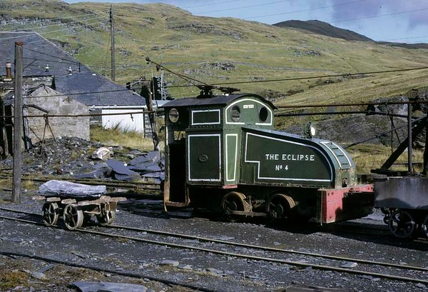 No 4 The Eclipse. Llechwedd slate quarry, Blaenau Ffestiniog, 5 October 1974 1.  The quarry had its own hydro-electric power station, and The Eclipse is a 2 foot gauge 0-4-0 overhead electric loco.   In 1927 it was converted at the quarry by J W Greaves from Bagnall 0-4-0ST 1445 / 1895.   In 2017 it was preserved out of use on the Welsh Highland Heritage Railway.  Photo by Les Tindall.