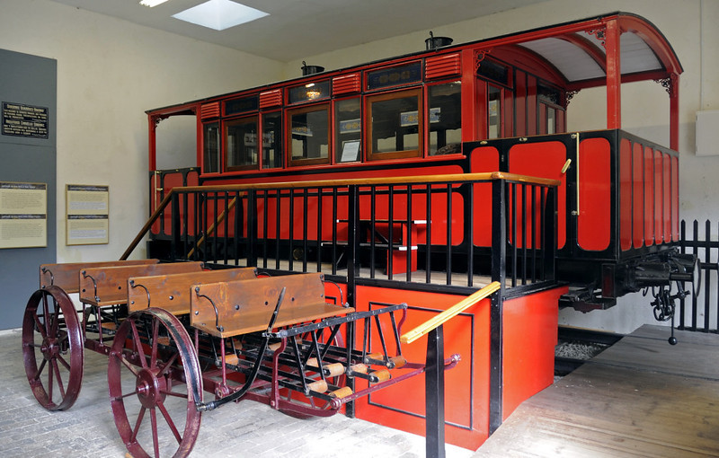 Dinorwig quarry saloon & Black Bess velocipede, Penrhyn Castle, Mon 22 August 2011.   The saloon was built in 1896 by the Gloucester Rly Carriage & Wagon Co to carry the Assheton Smith and Duff families on visits to the quarry, which they owned.  It was also used to carry the quarrymen's wages to the pay office under armed guard.   The velocipede is pedal operated.  Both vehicles ran on the 4ft gauge Padarn Rly.