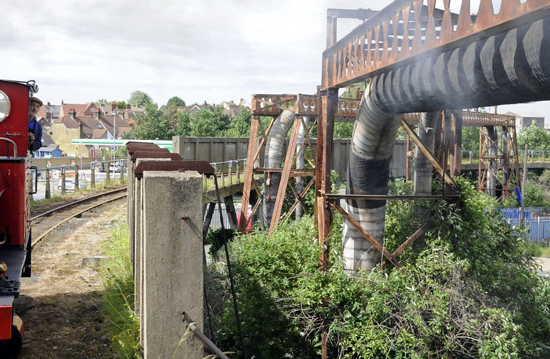 Leader, leaving Sittingbourne viaduct station, Sat 9 June 2012 - 1523.  The pipes used to carry steam, hot water and paper slurry from Kemsley mill to the Sittingbourne mill.  Now disused, they run alongside the SKLR for much of its length..