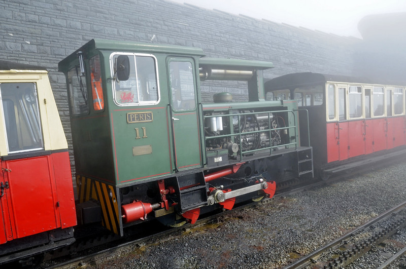Snowdon Mountain Rly No 11 Peris, Summit station, Sun 21 August 2011 - 1510.  The railway has bought four 320hp Hunslet diesels, Nos 9 & 10 in 1986 and Nos 11 & 12 in 1991.  Three diesel railcars bought in 1995 were not successful and have been scrapped.