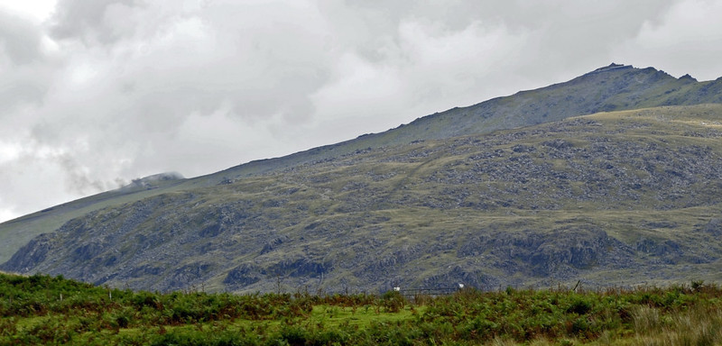 Snowdon, Mon 22 August 2011.  Smoke from a Mountain Rly train can be seen just below the skyline at left as it climbs to the 3561ft summit at right.  I took this shot from a Welsh Highland Rly train south of Rhyd Ddu.