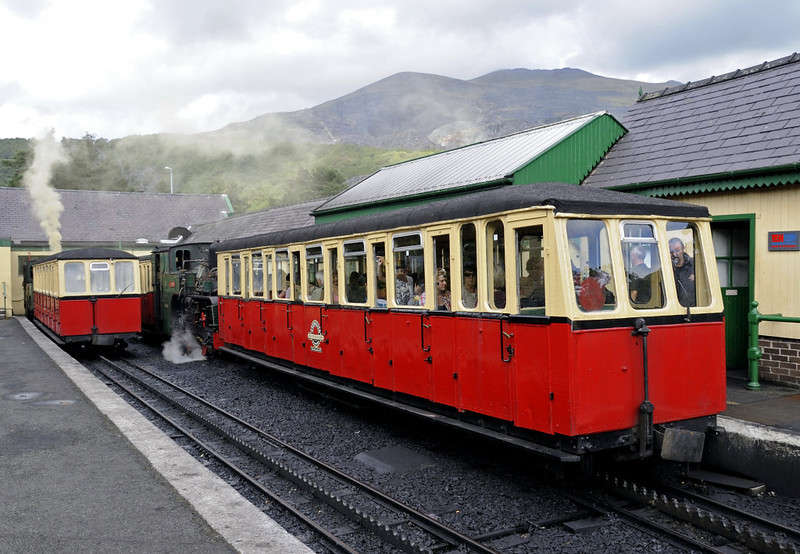 Snowdon Mountain Rly No 4 Snowdon (left) & No 6 Padarn, Llanberis, Sun 21 August 2011 - 1630.  No 11 Peris is out of sight behind Padarn.  The left hand platform is used for arrivals, the right hand one for departures.  Peris and Padarn had both shunted out of the arrivals platform.  Both carriages were amongst the six built by the Lancaster Rly Carriage & Wagon Co for the line's opening; five survive.