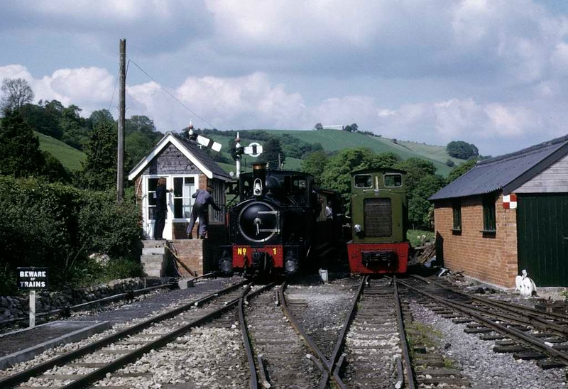 No 1 The Earl, Llanfair Caereinion, 27 May 1975.  The Earl's driver surrenders the token as his train enters the station, passing Chattenden, Baguley-Drewry 0-6-0DM 2263 / 1949 bult for the Admiralty.  Photo by Les Tindall.