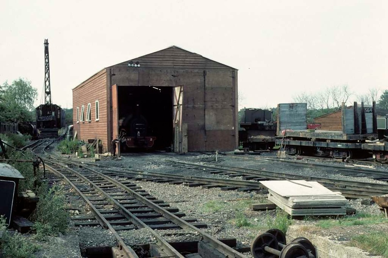 Loco shed, Whipsnade & Umfolozi Railway, 25 July 1976.  A dismantled loco is at right, behind the shed and flat wagon.  Note the mixed standard and two foot six inch gauge track in the foreground and at left.  Photo by Les Tindall.