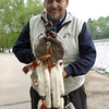 "May 26, 2006 When the fisherman I exchanged morning greetings with at Jamaica Pond noticed my camera, he said, ""Wait here, I have something to show you, something I made 53 years ago when I was twelve years old."" The item that C.O. Reese, aka Blackfoot Warrior, fetched from his van was this walking stick, topped with his totem, a hand-carved wooden bear; also decorated with brown rabbit fur, chicken hawk feathers, and white to represent the ermine. His birthstone, an amethyst, is imbedded in the handle. He uses the stick in his walks around his South End neighborhood. Blackfoot Warrior is a poet; his business card reads: ""The Creator Guides My Pen and Passages Come Out the Other End."""