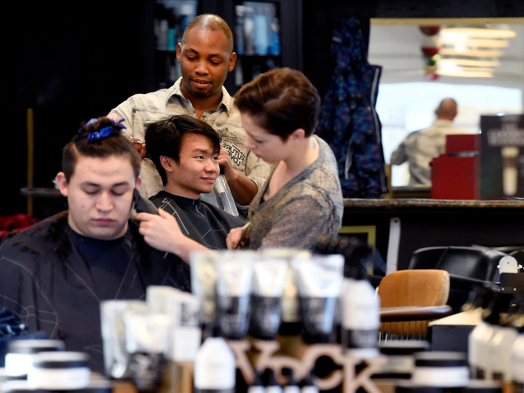 . BOULDER, CO - November 28, 2018:  Stacy Rahall cuts the hair of Jose Noriega, in the foreground, while Ja\'Mal Gilmore works on Sam Karman, n the background, at the Brooklyn Barber Academy in Boulder on November 28, 2018. (Photo by Cliff Grassmick/Staff Photographer)