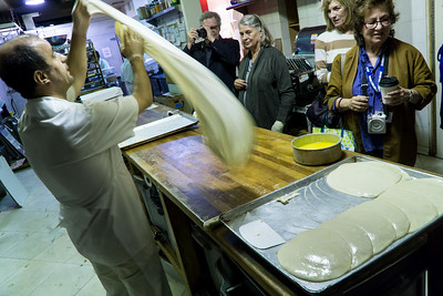 Then the chef starts with a new piece of dough, twirling it in the air to stretch it out and make it as thin as paper.