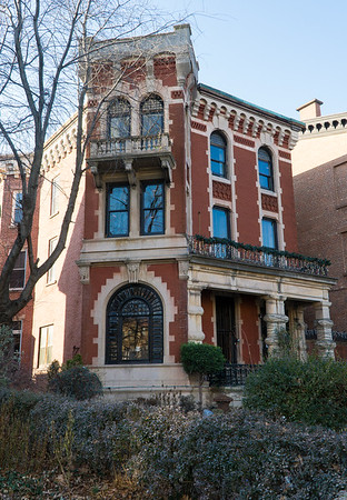 This brick mansion has a faceted front which faces the street and a section that's at an angle to the street with a magnificent arched window.