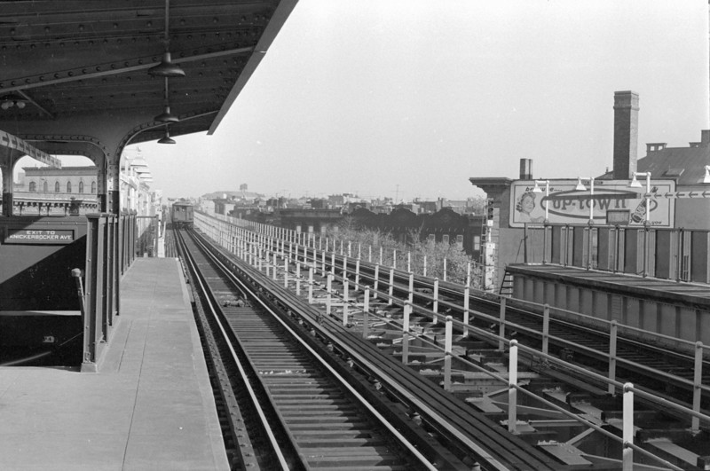 "Latter part of 1960, around the time of the fall of leaves.  The inbound train pulls into the Kinckerbocker Avenue Station.  On the right is Schwaben Hall, ""where the German elite meet."""