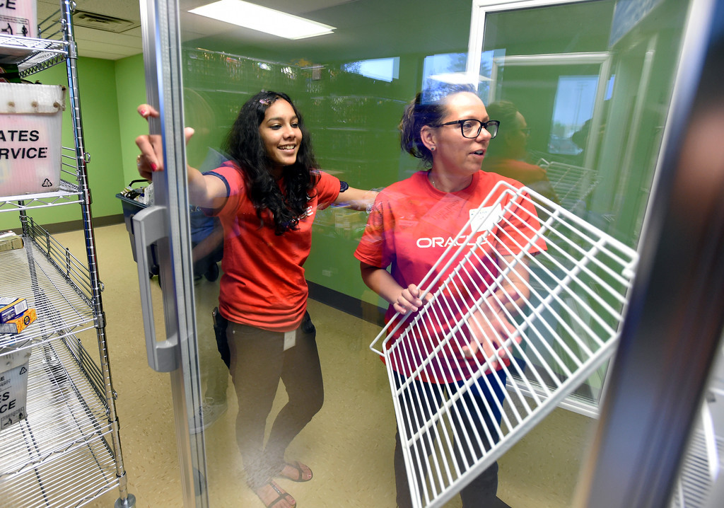 . Oracle volunteers Era Dwivedi, left, and Cyndi Gutowski  works to install shelving in a refrigerator at the new Broomfield Fish Food Pantry location on Thursday in Broomfield. For more photos of crews setting up the new food pantry location go to www.dailycamera.com Jeremy Papasso/ Staff Photographer/ May 25, 2017