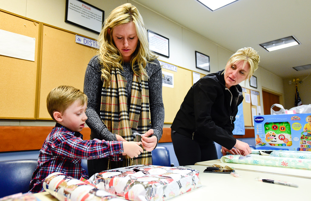 . Volunteers Chloe Durham, center, and her son Brayden Durham, 4, left, help wrap presets with Broomfield Police School Resource Officer Meredith Durham as part of the Santa Cops program in Broomfield, Colorado on Dec. 15, 2017. This year the program will serve 87 families including 225 children according to Broomfield Police Sgt. Steven Griebel. (Photo by Matthew Jonas/Staff Photographer)