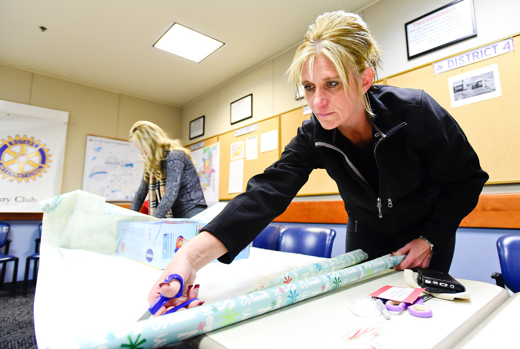 . Broomfield Police School Resource Officer Meredith Durham wraps gifts as part of the Santa Cops program in Broomfield, Colorado on Dec. 15, 2017. This year the program will serve 87 families including 225 children according to Broomfield Police Sgt. Steven Griebel. (Photo by Matthew Jonas/Staff Photographer)