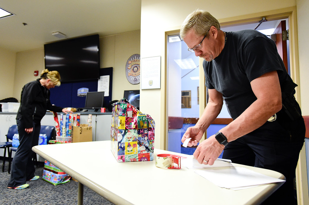 . Broomfield Police Sgt. Steven Griebel adds name tags to wrapped gifts in part of the Santa Cops program in Broomfield, Colorado on Dec. 15, 2017. This year the program will serve 87 families including 225 children according to Broomfield Police Sgt. Steven Griebel. (Photo by Matthew Jonas/Staff Photographer)