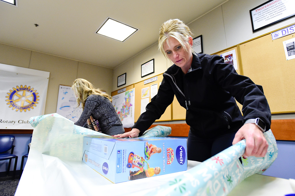 . Broomfield Police School Resource Officer Meredith Durham, right, and her daughter Chloe Durham, left, wrap gifts as part of the Santa Cops program in Broomfield, Colorado on Dec. 15, 2017. This year the program will serve 87 families including 225 children according to Broomfield Police Sgt. Steven Griebel. (Photo by Matthew Jonas/Staff Photographer)