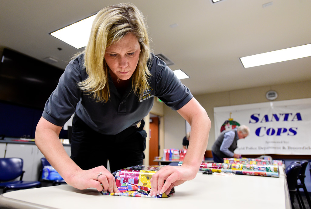 . Broomfield Police Proprety and Evidence Tech Carla Meszaros wraps a gift as part of the Santa Cops program in Broomfield, Colorado on Dec. 15, 2017. This year the program will serve 87 families including 225 children according to Broomfield Police Sgt. Steven Griebel. (Photo by Matthew Jonas/Staff Photographer)