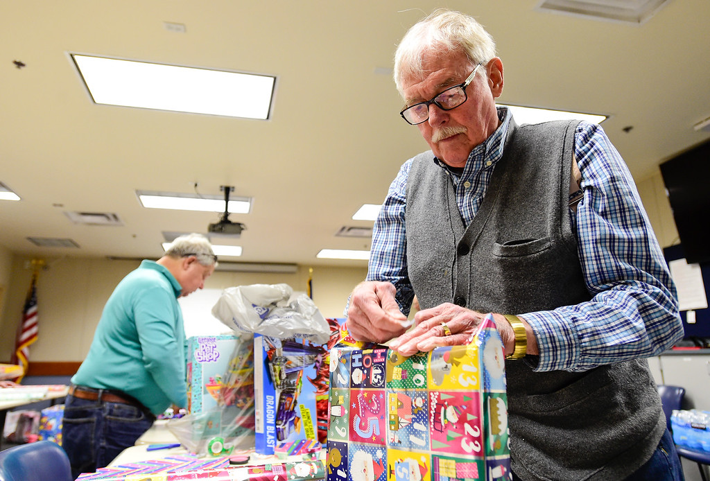 . Volunteer from the Rotary Club Carl Sauerland, right, wraps a gift as part of the Santa Cops program in Broomfield, Colorado on Dec. 15, 2017. This year the program will serve 87 families including 225 children according to Broomfield Police Sgt. Steven Griebel. (Photo by Matthew Jonas/Staff Photographer)